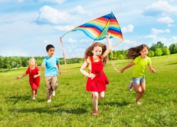 24234065-Group-of-four-kids-running-in-the-park-with-kite-happy-and-smiling-on-summer-sunny-day-Stock-Photo
